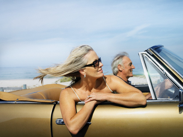 Couple Riding in Convertible on Oceanfront Road